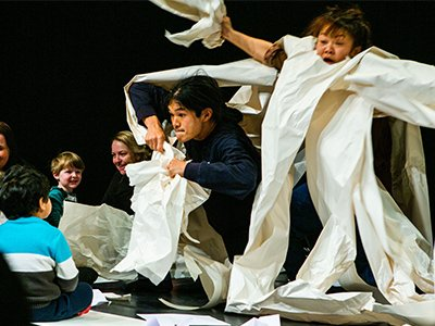 Two performers have lots of paper wrapped around them and flying through the air as a family audience watch smiling