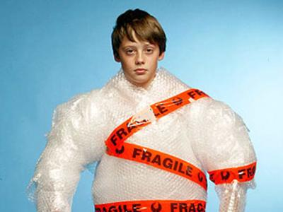 Cotton Wool Kids: an image with a young person standing with their arms to the side. They are wrapped up entirely in bubble wrap apart from their head and hands with the word fragile taped across them