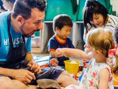 Creative Explorers: In a messy indoor playground, a dad reacts with exaggerated surprise as a child swings a toy in front of him