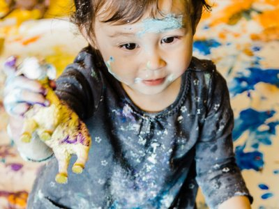A small child sits on a paint covered sheet. She is also covered in paint. She shows her hands to the viewer.