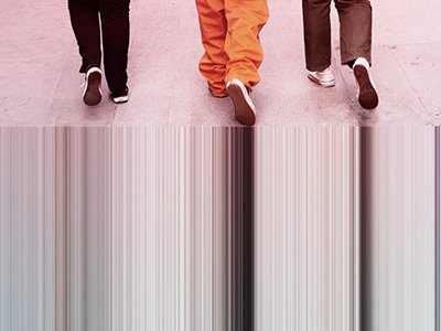 At the top of the image, 3 people wearing trainers are walking away from the camera, we can see the bottom half of their legs. They are walking on a grey pavement. On the bottom of the image, the shades of grey from the pavement are running down the scree