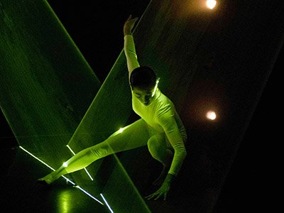 An image of a dancer dressed in white crouched on the floor with one hand on the floor and one stretched above them. They are lit in green and green lights also form plains of light around them.