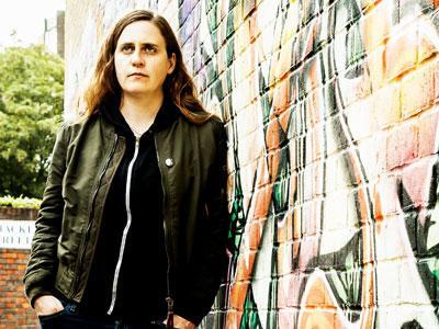 Dee Byrne leaning against a graffiti wall
