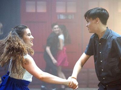Two young people are facing each other and holding hands while dancing