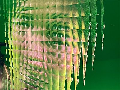 A pixelated image of a face, the colours are green and pink and it's been altered to make it appear as though the face has many eyes