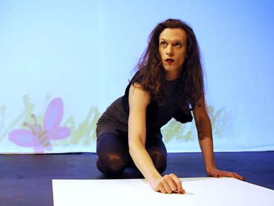 Edalia Day: A person kneeling on the floor of a stage, drawing on a white surface. The background is showing childish drawings of a house and a butterfly.