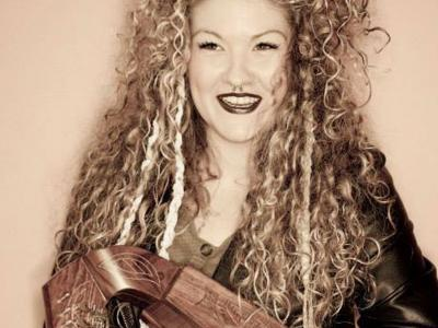 a sepia-tinted image of a woman's face. She has very curly blond hair framing her face, a septum piercing and darkly painted lips. She is smiling and holding a small harp.