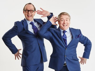 Eric and Ern: Two men in blue suits dancing with excited faces, one arm swinging to their head and the opposite leg lifted behind them
