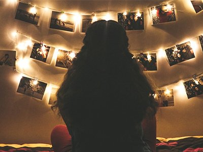 A person sits with their back to us facing a wall where polaroid photos and fairy lights are strung up