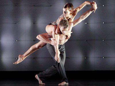Wayne McGregor: a woman stretches diagonally across a man's back