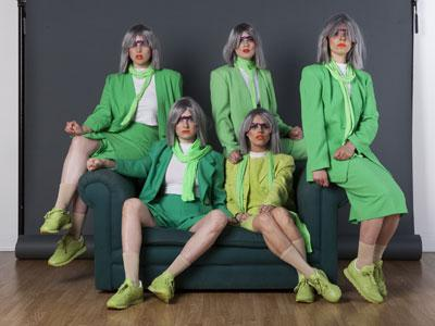 Figs in Wigs, dressed in green, draped on a sofa