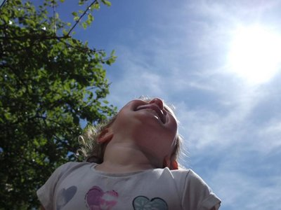 Fly High Stories: a photograph of a girl looking up into the blue sky and bright sun