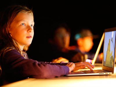A girl sits in a darkened room on a laptop. The light from the laptop lights up her face.