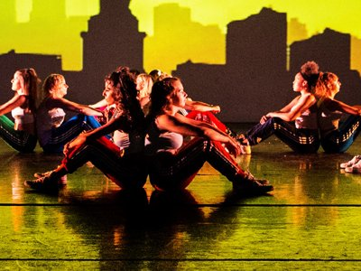 Give Into Dance - pairs of dancers sitting back to back on stage lit in bright yellow. The backfrop shows the skyline of New York