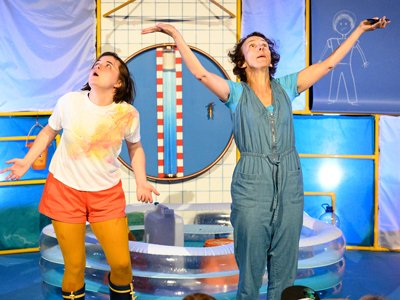 Two women stand in a room, all brightly coloured in yellow and blue. They both look to the sky, hands facing upwards.