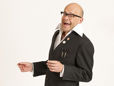 Harry Hill is wearing a black suit with a large white shirt collar. He is looking at the camera and is pictured from the waist up.