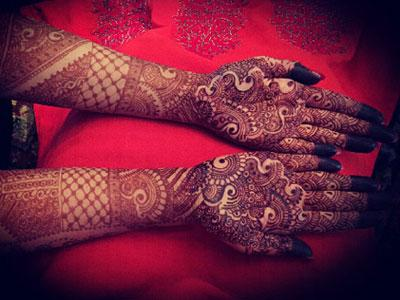 An image of hands painted in henna with a red background.