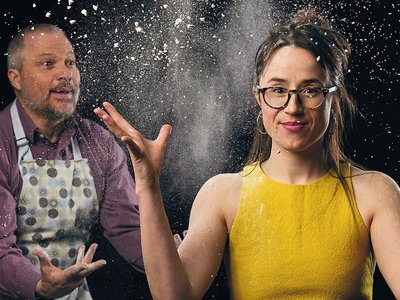 A woman in a yellow top throws flour up around herself. A man behind her throws flour at her.