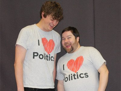 "Two men in ""I Love Politics"" t-shirts pose together. One makes an excited face towards the camera, while the other one is laughing"