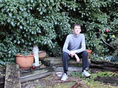 A young man sitting in a green garden