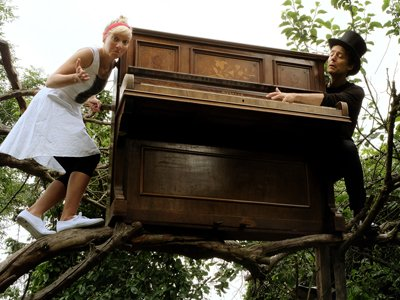 A man in black tie and a top hat and a woman in a white dress are stood in a tree with an upright piano.