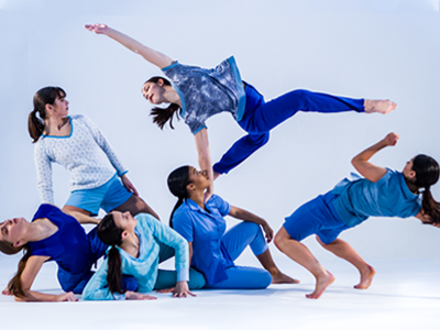 a blue-tinted image of a group of 6 dancers. They sit, stand and jump, reaching away from each other to form a fan-shaped formation.