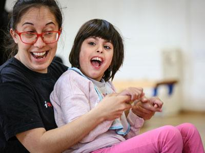 Photo of a girl sitting on the knee of a woman, both smiling and dancing