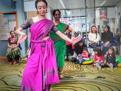 Two dancers in traditional Indian dress perform in front of an audience of families