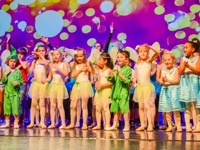 Innovation Dance: a row of children in fairy costumes stand on a stage, the background is lit up in multi-colour LEDs