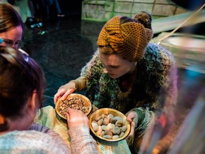 The Isle of Brimsker: a woman in cozy knitwear shows a bowl of pebbles to a participant