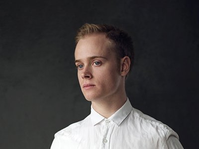 A young person with blonde hair and blue eyes looks off in front of a grey background