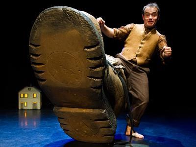 a man raising a foot stuck in an enormous shoe