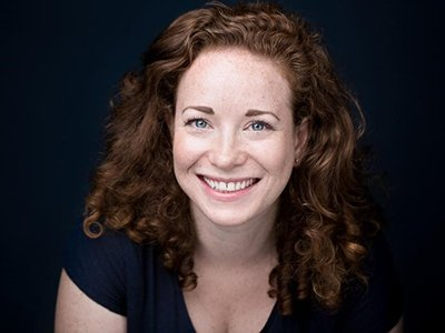 An image of Jemma Gross, a white woman with curly red hair and a big smile. She is looking at the camera.