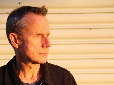 Jeremy Hardy against a sunset-lit wall