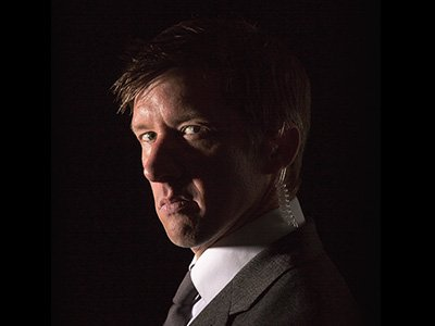 Jonathon Pie wears a suit and looks with scorn against a darkened background