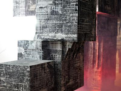 An image of sculptures of brutalist-inspired buildings covered with newspaper text by Joseph Goddard