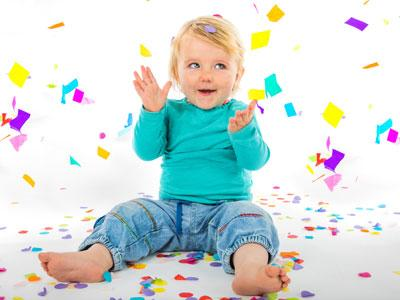 a toddler dressed in blue sitting amidst of falling glitter