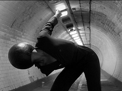 A dancer is in an underground tunnel they wear a black suit and a black dome covers their head
