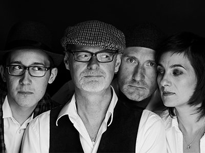 Black and white image of four performers all with their heads close together