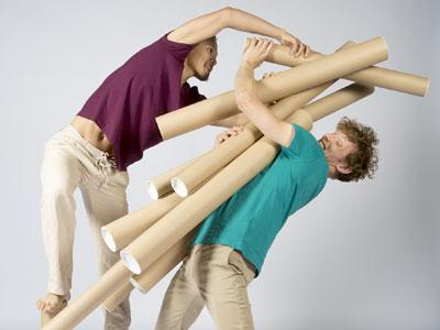 Two men playing with cardboard tubes, one of them just about to be buried under the tubes