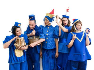 A group of people in electric blue costumes with pointy hats holding instruments