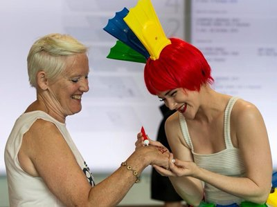 A women with a red wig, from which small red, blue and yellow flippers emerge, is drawing on the hand of a woman with short white hair in a tank top. They both look very happy.
