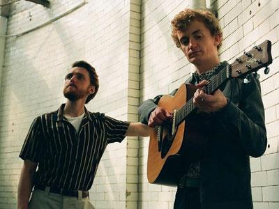 A photo of two men playing the guitar in a room with white subway tiles lining the wall.