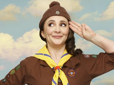 Lucy Porter, dressed as a brownie is giving the brownie salute