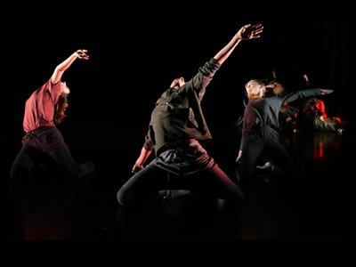 MDX Dances: a dark black image with three dancers in colour, they are jumping and turning with one arm in the air