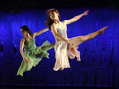 Two female dancers jumping in front of a dark blue background