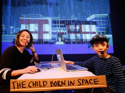 MINE: Maiko Yamamoto and Hokuto sit on a table with laptops. They are wearing head mics and smiling. The screen behind them shows a pixelated rainy landscape.