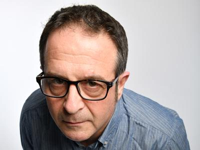 Mark Thomas NHS at 70: Mark Thomas, in a blue shirt, leaning forward and looking quizzically into the camera
