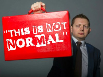 "Matt Chorley: A man in a suit holds up a red briefcase that's labelled ""This is not normal"""