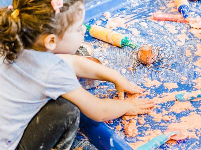 a child playing in a colourful mess